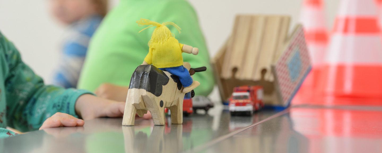 Kinder spielen mit Kühen und Feuerwehrauto